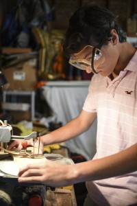 Logan Leppo '17 uses a band saw to cut one-inch thick pieces of pine for a toy dog.