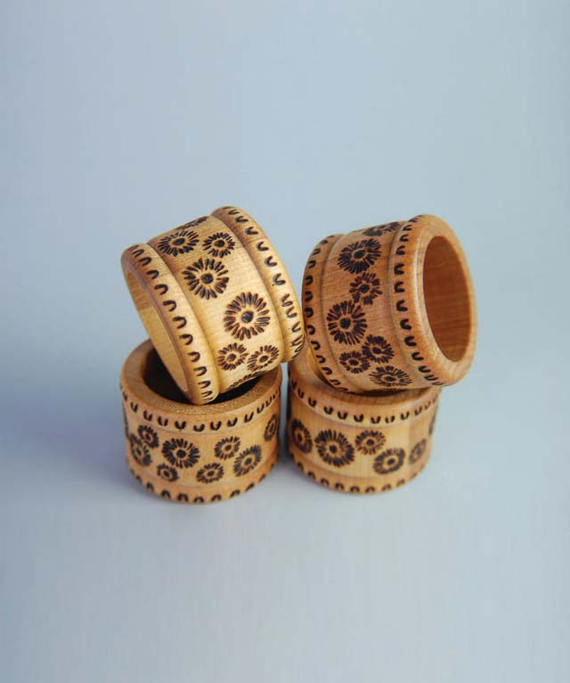 Si decorated these napkin rings with simple daisy designs and patterned borders, made by pressing different tip shapes into the wood.